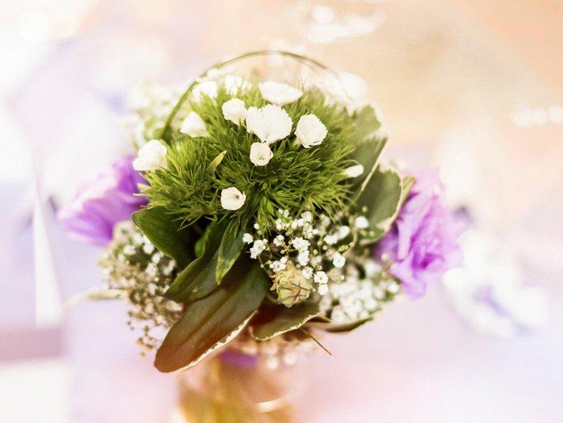 Die Blumenarrangements der Tischdekoration sind auf dieser Hochzeit sehr schlicht gehalten