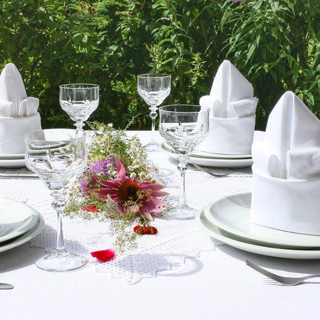 gedeckter Tisch mit zur Lilie gefalteten Stoffservietten