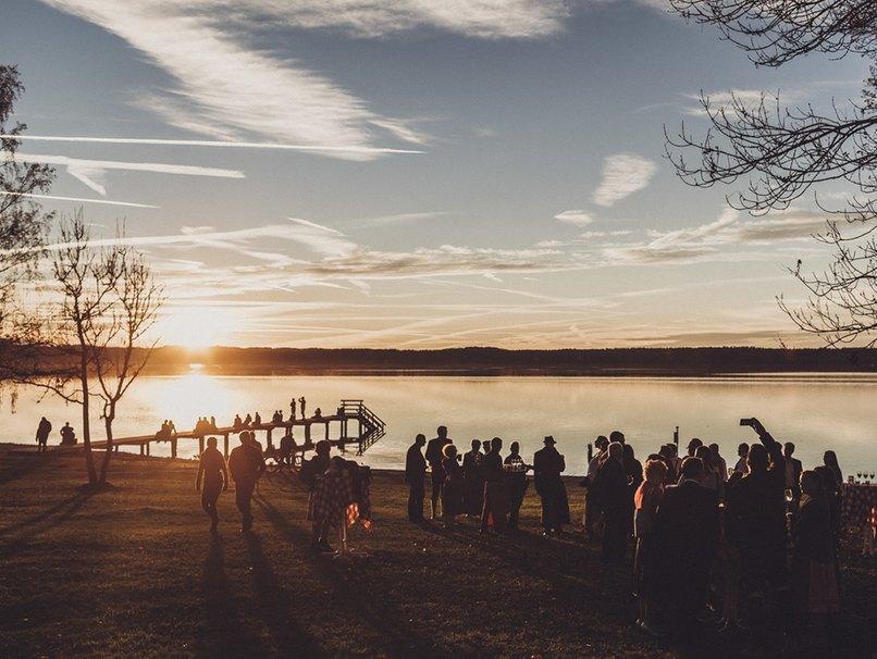 Hochzeitsgesellschaft bei Sonnenuntergang am See